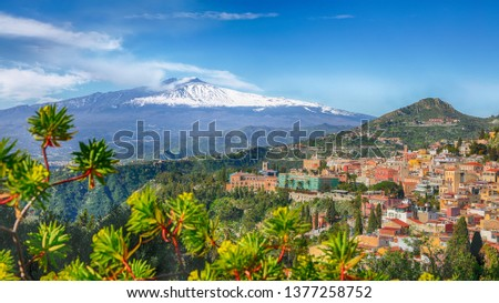 Etna volcano and Taormina town aerial panoramic view. Roofs of a lot of buldings. Smoking snow-capped Mount Etna volcano. Taormina, Sicily, Italy. #1377258752