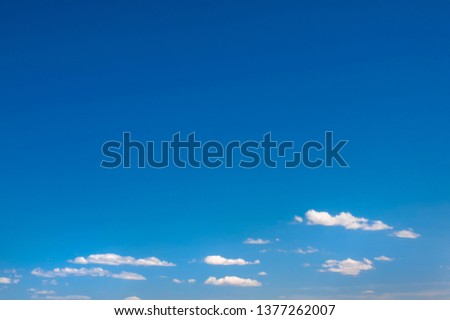 Deep blue sky at the top of the image with fluffy clouds at the base. Suitable as a background with lots of copy space.   #1377262007