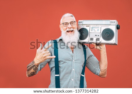 Happy senior man listening to music with boombox outdoor - Crazy hipster male having fun dancing with vintage stereo - Concept of elderly people lifestyle #1377314282