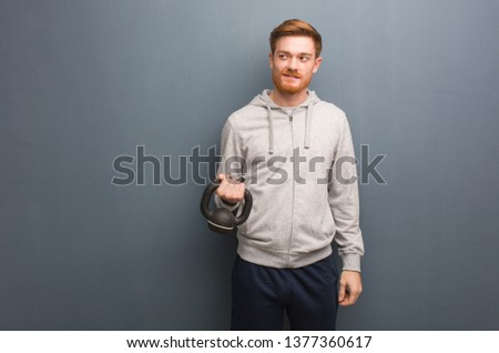 Young redhead fitness man smiling confident and crossing arms, looking up. Holding a dumbbell. #1377360617