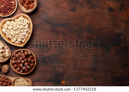 Various nuts selection: peanuts, hazelnuts, chestnuts, walnuts, pistachio and pecans on wooden table. Top view with space for your text #1377402218