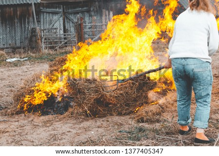 grass is burning on the street. the fire is very big. ordinary resident trying to extinguish the fire with a pitchfork #1377405347