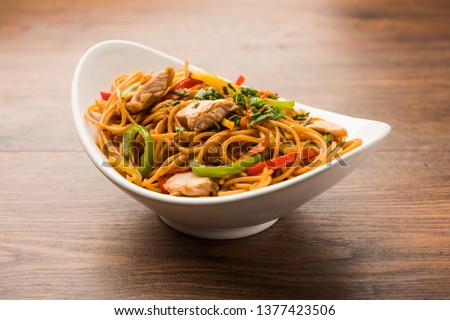 Chicken Hakka/Schezwan noodles served in a bowl with chopsticks. selective focus #1377423506
