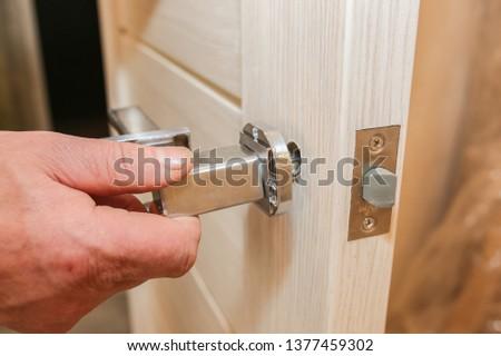 Man is installing the doors handle. Repair works. Maintenance in the apartment. Renovation. #1377459302