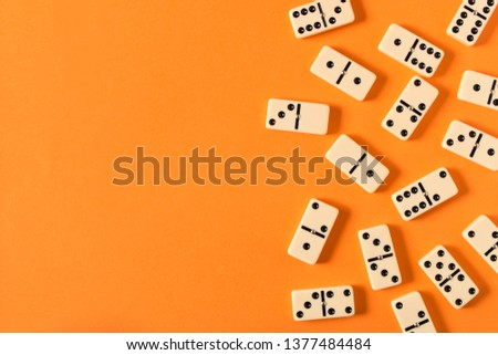 Playing dominoes on a orange table. Domino effect #1377484484
