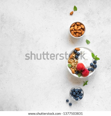 Granola with yogurt and berries for healthy breakfast. Bowl of greek yogurt with granola, almonds, blueberries and strawberries, top view, copy space. #1377503831