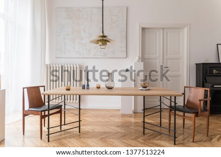 Eclectic and elegant dining room interior with design sharing table, chairs, gold pendant lamp, abstract paintings, piano and stylish accessories. Minimalistic decor. Brown wooden parquet. Real photo. #1377513224