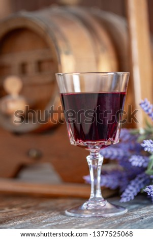 A glass of red wine and a bouquet of lavender flowers next to a wine wooden barrel. Art photography. Closeup. Soft focus.Toned image doesn't in focus. #1377525068