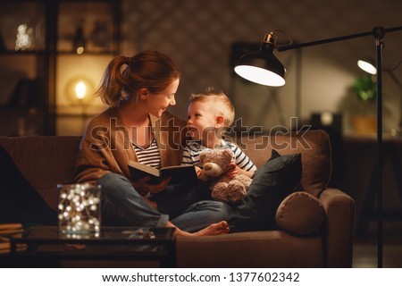 Family before going to bed mother reads to her child son book near a lamp in the evening #1377602342