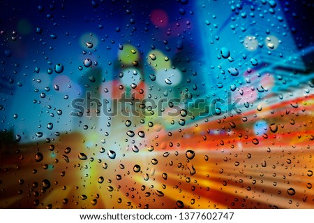 Rainy day. Raindrops on a blurred multicolored bokeh background #1377602747