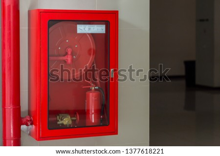 Hydrant with water hoses and fire extinguish equipment. Fire safety equipment in the red box on wall cement . Hydrant with water hoses and fire extinguish equipment / fire hose box . #1377618221