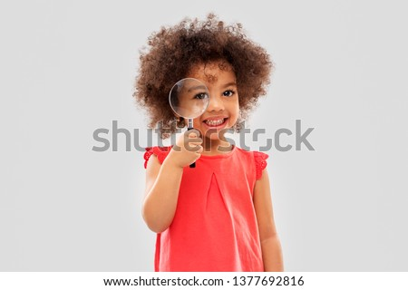investigation, discovery and vision concept - happy little african american girl looking through magnifying glass over grey background #1377692816
