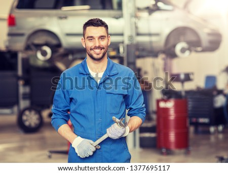 car service, repair, maintenance and people concept - auto mechanic man or smith with wrench at workshop #1377695117