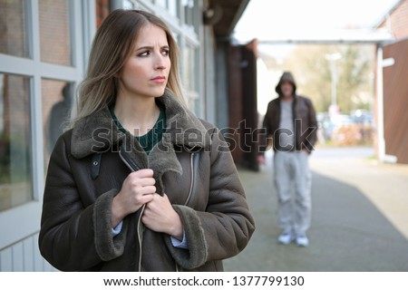 Woman looks frightened because a stalker follows her #1377799130