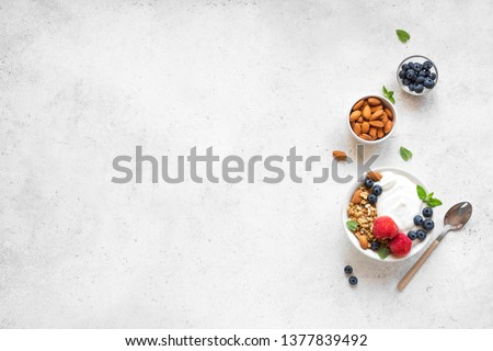 Granola with yogurt and berries for healthy breakfast. Bowl of greek yogurt with granola, almonds, blueberries and strawberries, top view, copy space. #1377839492