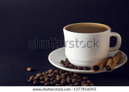 White cup of hot coffee and Cinnamon sticks isolated on black background. #1377856043