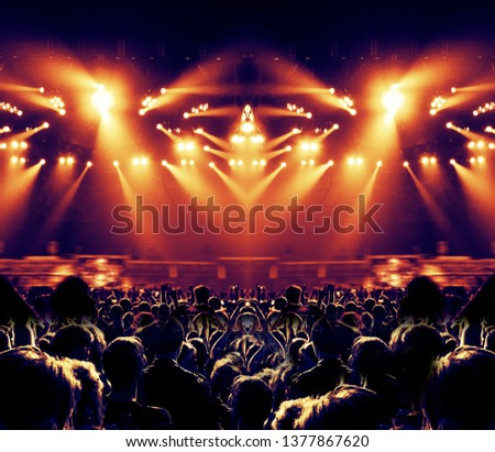 Concert image with people standing in front of a stage lit for the music festival show #1377867620
