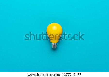 flat lay photo of yellow bulb on turquoise blue backgound. top view of lightbulb in the center of the shot with copy space. minimalist picture of yellow painted electric lamp #1377947477