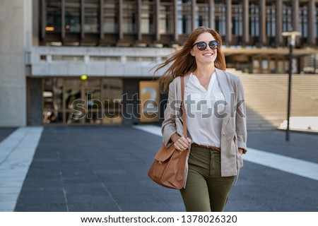 Portrait of successful happy woman on her way to work on street. Confident business woman wearing blazer carrying side bag walking with a smile. Smiling woman wearing sunglasses and walking on street. #1378026320