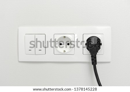 Electrical sockets on the wall with black connection plug and white switch.  Royalty-Free Stock Photo #1378145228