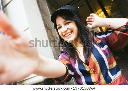 Happy laughing mixed race woman in a multi-colored striped dress makes selfie #1378150964