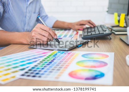 Image of male creative graphic designer working on color selection and drawing on graphics tablet at workplace with work tools and accessories in workspace. #1378199741
