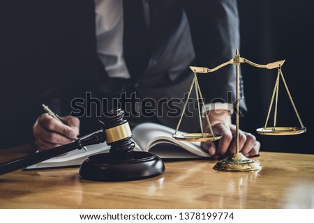 Male lawyer or judge working with contract papers, Law books and wooden gavel on table in courtroom, Justice lawyers at law firm, Law and Legal services concept. #1378199774