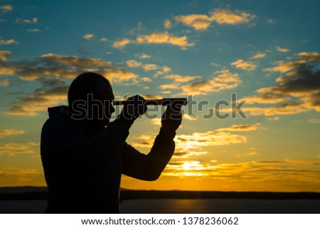 A man looks into a use monocular telescope against a dramatic sky at sunset. business concept idea, look to the future, look, spy. Businessman. Vision #1378236062