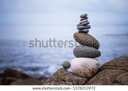Close up picture of a stone cairn outdoors. Ocean in the blurry background #1378253972