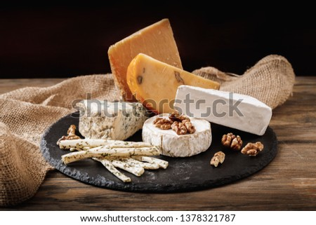 Different types of cheeses. slices of cheese brie or camembert with parmesan, cheddar ,blue cheese , and other with nut and honey on wooden board on dark background #1378321787