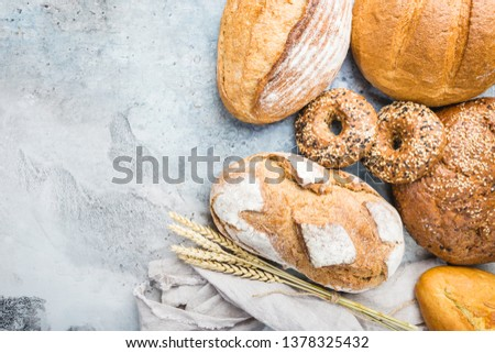 Assortment of fresh baked bread and buns on stone background, top view #1378325432