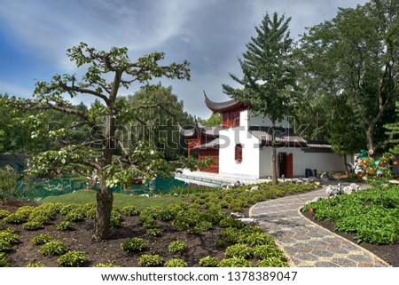 MONTREAL, CANADA, September 5, 2018: Beautiful small pine tree growing in yellow flowerbed with pond and pretty pavilion in Montreal s Botanical Gardens, Montreal, Quebec #1378389047
