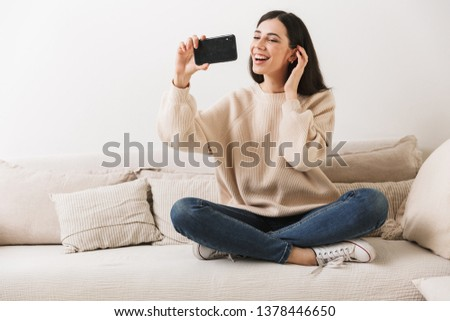 Photo of charming caucasian woman 20s smiling and holding cell phone while sitting on sofa at home #1378446650