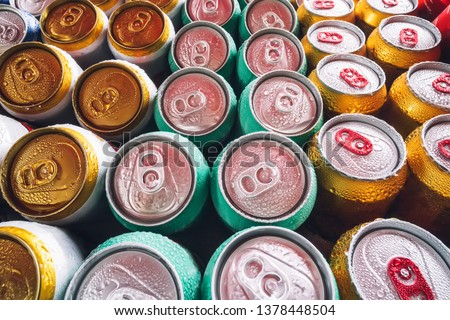 Metal cans of beer with ice cubes in mini refrigerator, close up. Lots of aluminum cans in the ice in the open fridge. Drops of water on a cold can of drink. #1378448504