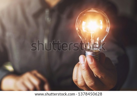 hand holding light bulb. idea concept with innovation and inspiration #1378450628
