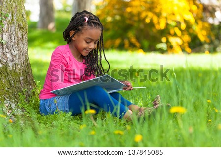 Outdoor portrait of a cute young black little  girl reading a book - African people #137845085