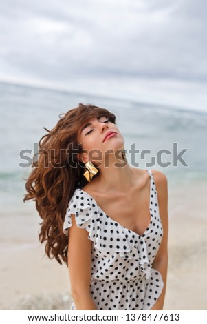 A beautiful girl with wavy brown hair, dressed in a polka-dot dress, stands on the seashore, and with her eyes half-closed, she throws her hair back #1378477613