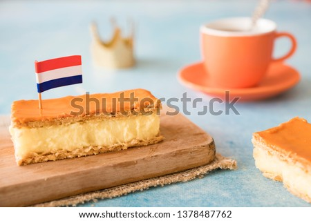 Orange tompouce, traditional Dutch treat with pudding and frosting on national holiday Kings Day (April 27th), in The Netherlands. With cup of tea, and Dutch flag #1378487762