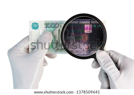 Investigeting counterfeit money. Hands in white gloves with x ray magnifier over 1000 rubles banknote isolated on white background #1378509641