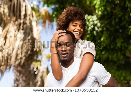Outdoor protrait of black african american couple - Guy carrying girfriend on his back #1378530152