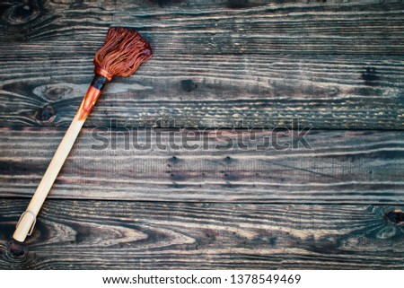 BBQ Mop or brush over top a rustic wood table / background with barbecue sauce on end. Image shot from overhead view.