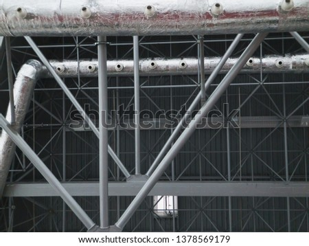 Stadium ventilation system and fire extinguishing system between the steel roof supports standing on concrete beams. Complex multi-system engineering structures. #1378569179
