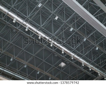 Stadium ventilation system and fire extinguishing system between the steel roof supports standing on concrete beams. Complex multi-system engineering structures. #1378579742