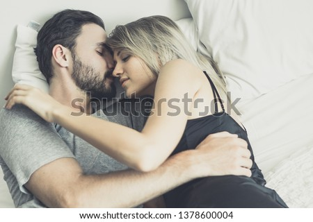 Loving happy couple in love smile and hug each other on the bed, in big bedroom, Love story concept #1378600004