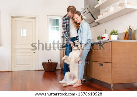 Young happy married couple in love spend a weekend together with their smart white purebred dog standing in the kitchen of country house. Family time concepts #1378610528