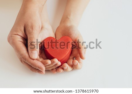 Mother and son holding red heart in their hands on white background. Mother's Day concept. International Heart Day concept.  #1378615970