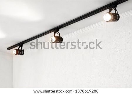 Spotlights under the ceiling on the wall. Track LED-lighting system. #1378619288