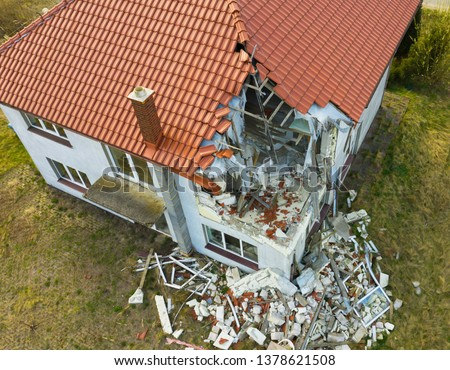 Aerial view on damaged red single house roof after strong wind or explosion. Hole in the rooftop and floor. Rubble on the ground. #1378621508