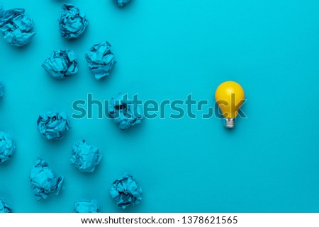 new idea concept with crumpled office paper and light bulb. top view of great business idea concept over blue background. creative solution during brainstorming session concept #1378621565
