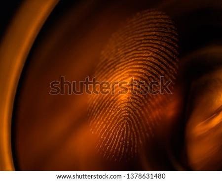 Fingerprint macro on a lens in red light, shallow depth of field. Fingerprint scanning, biometrics and security concept. #1378631480
